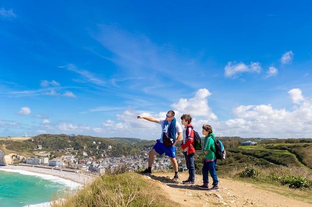 Ojciec i dwóch synów podróżujący razem i wędrujący po malowniczych górach. pojęcie turystyki rodzinnej
