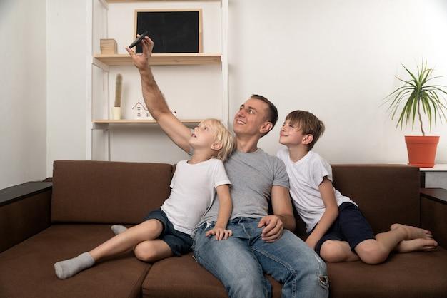 Ojciec i dwóch synów robią selfie, siedząc na kanapie. wypoczynek z dziećmi.