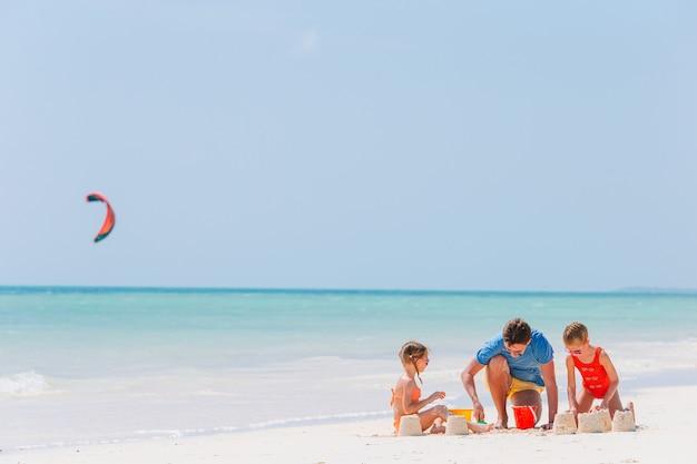 Ojciec i dzieci co zamek z piasku na tropikalnej plaży. rodzina bawi się zabawkami na plaży