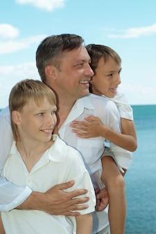 Ojciec i dzieci na tle morza