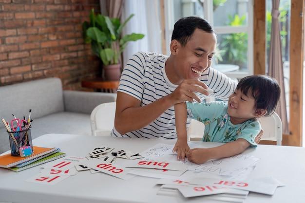 Ojciec i dziecko dobrze się bawią razem ucząc się