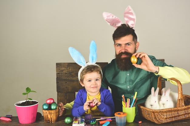 Ojciec i dziecko maluje pisanki. rodzina królika z uszami królika. ładny mały chłopiec dziecko ubrany na wielkanoc.