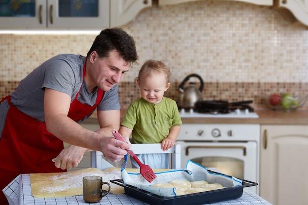 Ojciec i dziecko pieczą ciasta, gotują i bawią się w kuchni. domowe jedzenie i mały pomocnik. szczęśliwe rodzicielstwo.