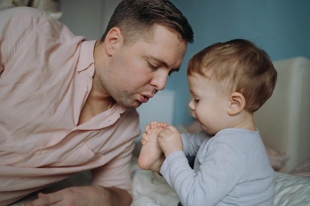 Ojciec i dziecko w domu dziecko zraniło palec u nogi tata dmuchanie, aby złagodzić ból koncepcja rodzinnej miłości i opieki