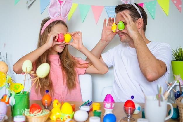Ojciec i jego córeczka maluje jajka szczęśliwa rodzina przygotowuje się do wielkanocy