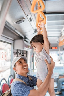 Ojciec i jego córka bawią się podczas jazdy transportem publicznym wiszący na kierownicy