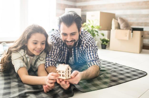 Ojciec i jego córka leżą na kocu na podłodze. trzymają dom samm wykonany z drewna. patrzą na to i uśmiechają się.