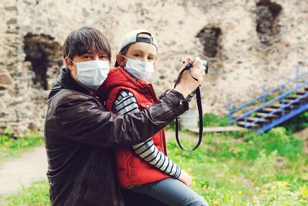 Ojciec i jego syn biorąc zdjęcie starego zamku. rodzinna jest ubranym twarzy maska na zewnątrz. tata i dzieciak razem.