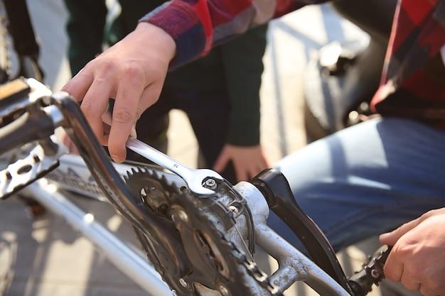 Ojciec i jego syn naprawiają rower na świeżym powietrzu, zbliżenie