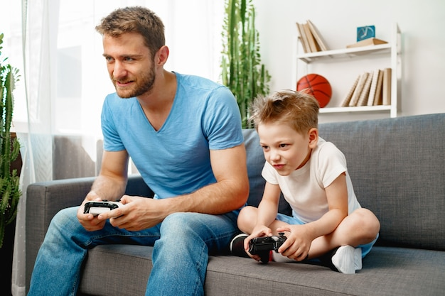 Ojciec i jego synek razem grają w gry wideo na kanapie w domu
