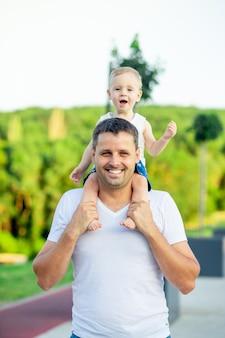 Ojciec i jego synek spacerują latem po parku w zachodzącym słońcu i uśmiechają się podczas zabawy, ojciec trzyma syna na szyi