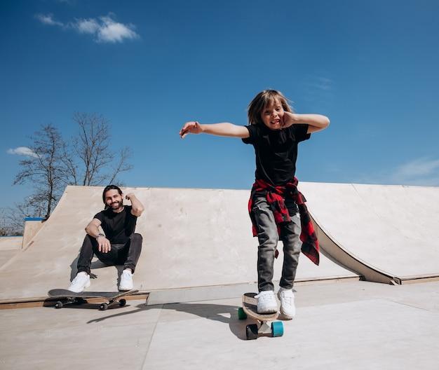 Ojciec i jego synek ubrani w zwykłe ubrania jeżdżą na deskorolkach i bawią się w skateparku ze zjeżdżalniami na zewnątrz w słoneczny dzień.