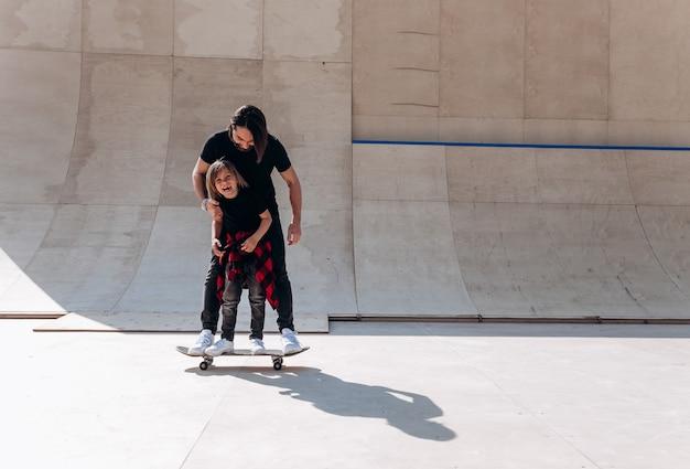 Ojciec i jego synek ubrani w zwykłe ubrania stoją razem na jednej deskorolce w skateparku w słoneczny dzień.