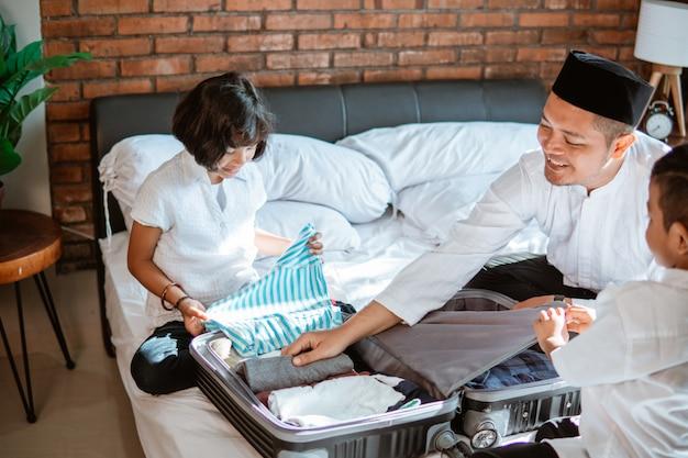 Ojciec i jej dziecko przygotowują ubrania w walizce