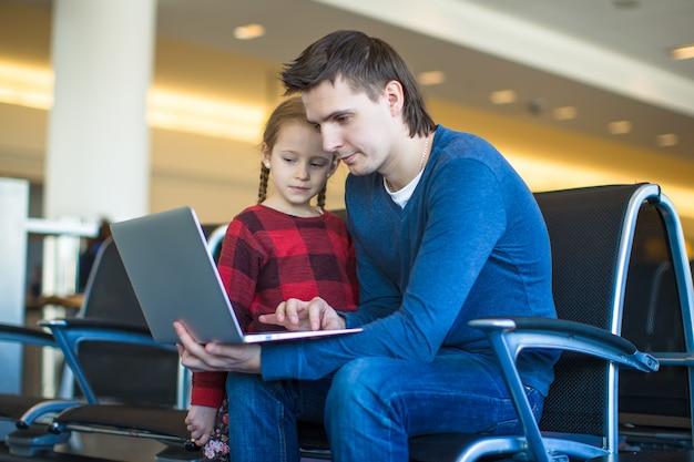 Ojciec i mała dziewczynka z laptopem przy lotniskiem podczas gdy czekający jego lot