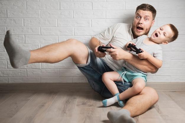Ojciec i mały chłopiec bawi się ze swoimi kontrolerami