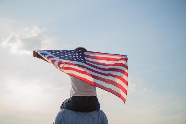 Ojciec i mały chłopiec trzyma amerykańską flagę