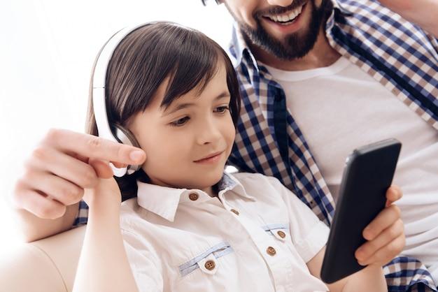 Ojciec i mały syn w słuchawkach słuchają muzyki.