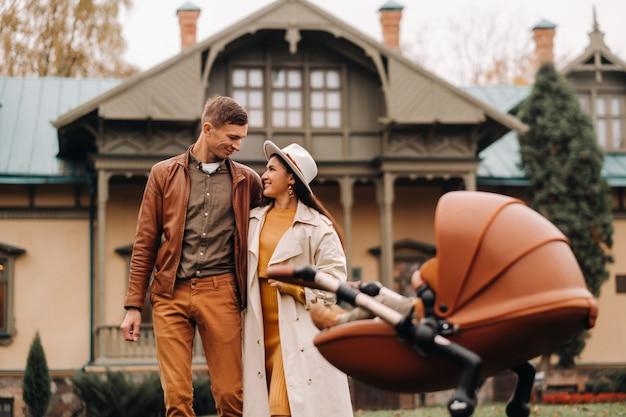 Ojciec i mama na spacerze z dzieckiem w wózku w jesiennym parku na tle osiedla. rodzina spaceruje po parku krajobrazowym złota jesień.