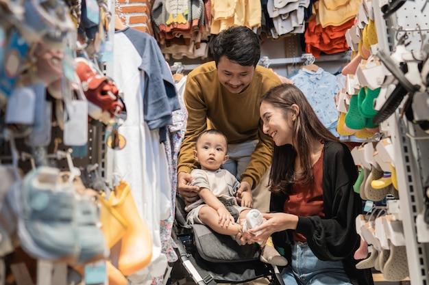 Ojciec i mama robią zakupy w sklepie dla dzieci z synem w wózku