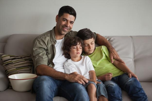 Ojciec i śpiący synowie z miski popcorn oglądania telewizji w salonie
