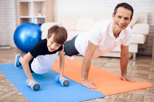 Ojciec i syn angażują się w fitness wraz z fitballem.