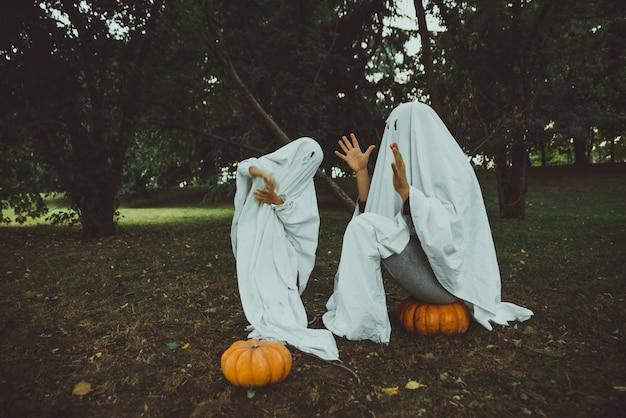 Ojciec i syn bawią się duchami z białymi prześcieradłami w ogrodzie, koncepcyjne zdjęcia z halloween