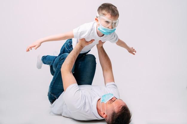 Ojciec i syn bawią się podczas kwarantanny w maskach medycznych.