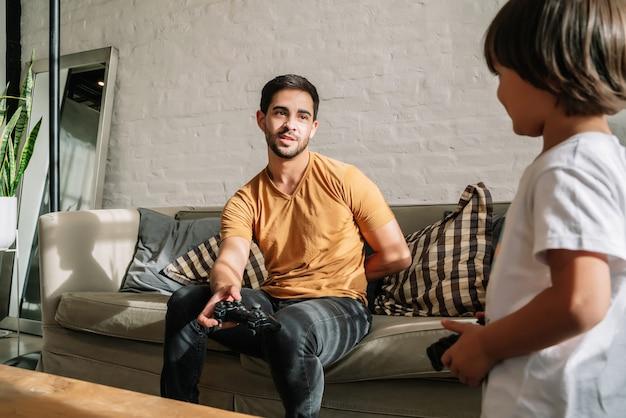 Ojciec i syn bawią się razem grając w gry wideo w domu. koncepcja rodziny jednorodzicielskiej.