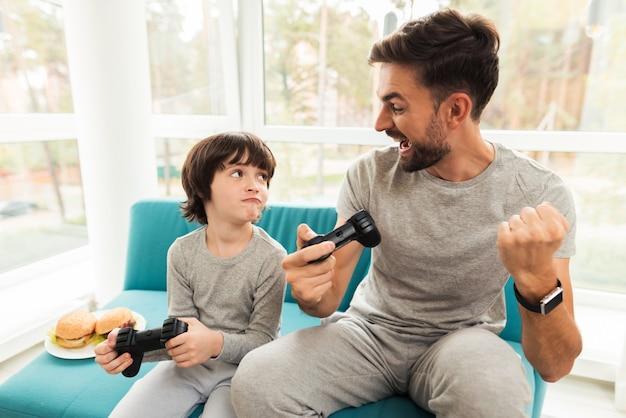 Ojciec i syn bawią się razem w grach komputerowych.