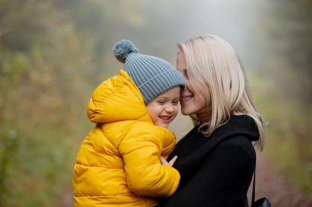 Ojciec i syn bawią się w jesiennym lesie we mgle