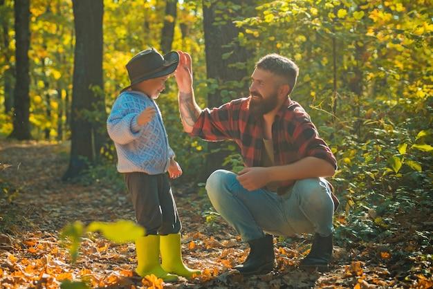 Ojciec i syn bawią się w lesie jesienią. mały chłopiec rozmawia z ojcem jesienią na zewnątrz
