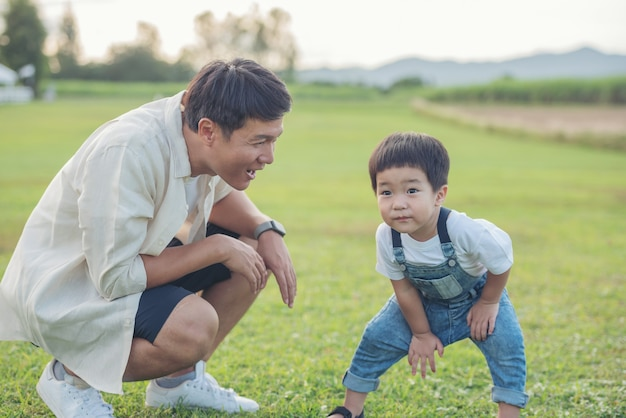 Ojciec i syn bawią się w parku w czasie zachodu słońca. ludzie bawiący się na boisku. koncepcja przyjaznej rodziny i letnich wakacji. nogi ojca i syna spacerują po trawniku w parku