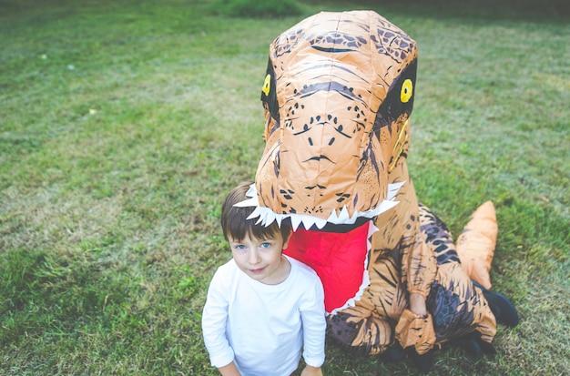 Ojciec i syn bawią się w parku z kostiumem dinozaura, bawiąc się z rodziną na świeżym powietrzu