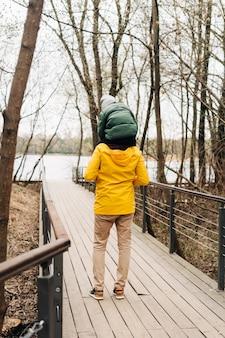 Ojciec i syn bawią się z przejażdżką na barana w lesie szczęśliwa rodzina z dzieckiem chłopiec bawi się i