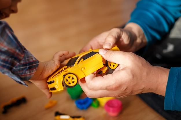 Ojciec i syn bawią się zabawkami maszyn