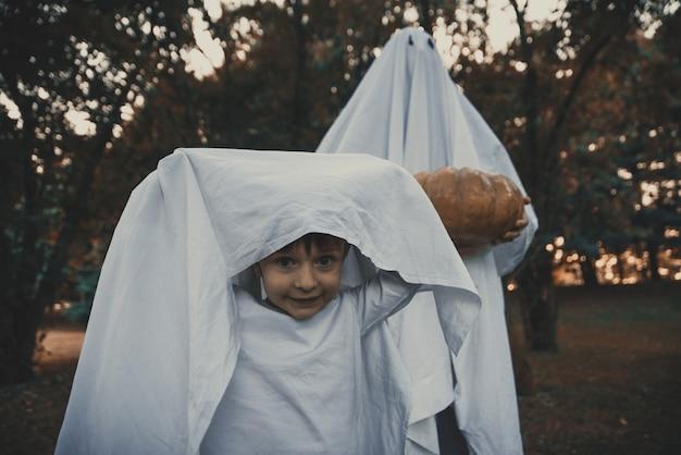 Ojciec i syn bawiące się duchy z białą pościelą w ogrodzie
