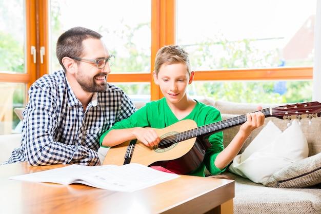 Ojciec i syn bawić się gitarę w domu