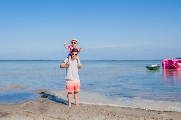 Ojciec i syn bawić się na plaży w czasie dnia