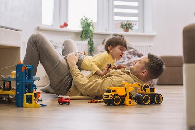 Ojciec i syn bawić się na podłogowym długim strzale