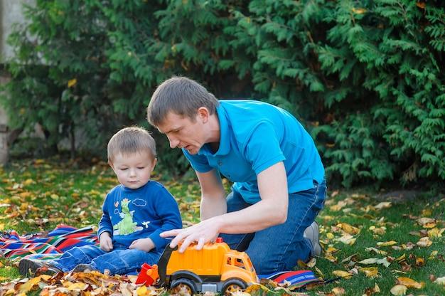 Ojciec i syn bawić się w parkowym zabawkarskim samochodzie w parku na trawie w jesieni