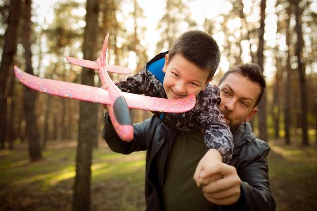 Ojciec i syn chodzą i bawią się w jesiennym lesie, wyglądają na szczęśliwych i szczerych