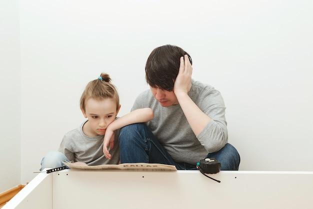 Ojciec i syn czytają instrukcję montażu mebli w nowym domu. zrób to sam montaż mebli. syn pomaga ojcu w montażu mebli w domu.