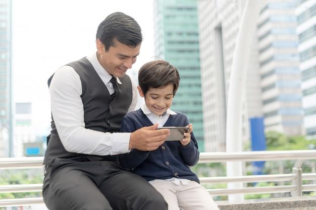 Ojciec i syn gra gra inteligentny telefon razem na dzielnicy biznesowej miejskich