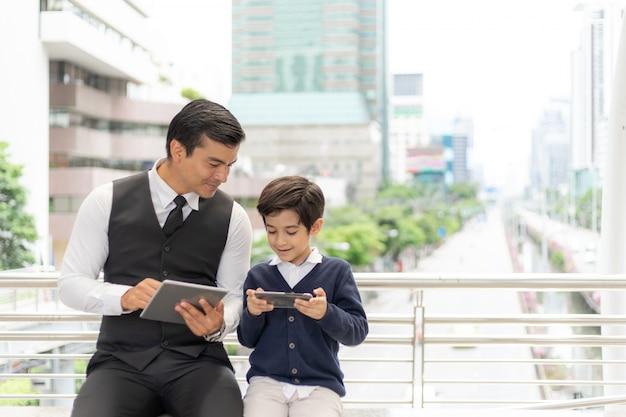 Ojciec i syn gra razem inteligentny telefon, tata i syn szczęśliwy koncepcja rodziny