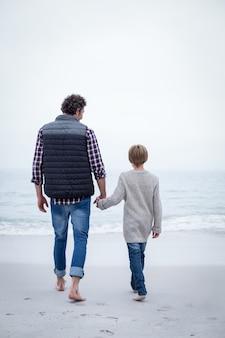 Ojciec i syn idzie w kierunku brzegu morza