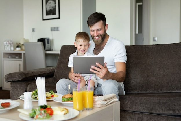 Ojciec i syn jedzą śniadanie w pokoju hotelowym i patrzą na laptopa.
