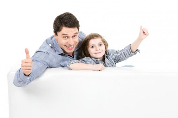 Ojciec i syn kciuk siedząc na kanapie