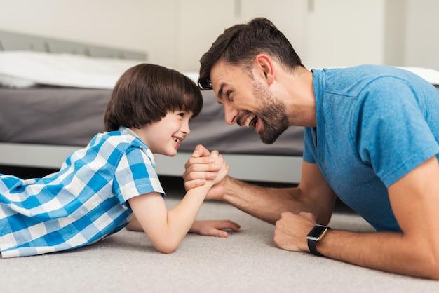 Ojciec i syn leżący na podłodze i baw się dobrze w domu