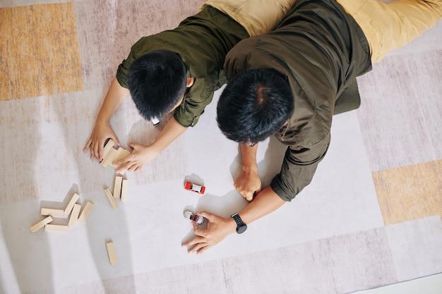 Ojciec i syn, leżący na podłodze i bawiący się zabawkami samochodowymi i drewnianymi klockami, widok z góry